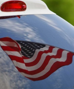 A photo of an American flag reflecting in an emergency vehicle windshield.