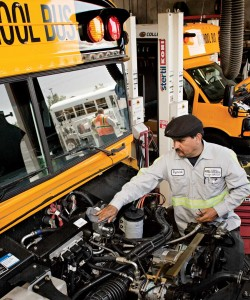 A photo of a mechanic working on a propane powered bus.