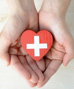 A photo of hands holding a crafted heart with the medic cross symbol.