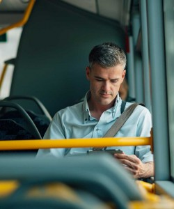 A photo of a gentleman reading in a propane powered bus.